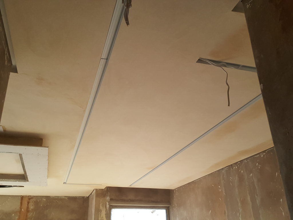 Suspended bulkhead with strip light effect above bed